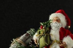 Santa Claus die een zak naast logboekbundel houden op een zwarte achtergrond met het schrijven van ruimte stock foto