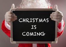 Santa Claus die een zwart die schoolbord houden met KERSTMIS wordt geschreven KOMT Stock Foto