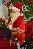 Santa Claus, die ein Buch liest, während eine Elfe neben ihm hilft Stockbild