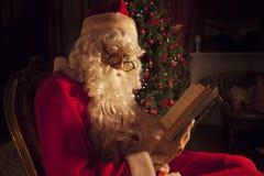 Santa Claus, die ein Buch sitzt in einem Stuhl liest Lizenzfreie Stockfotografie
