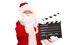 Santa Claus, die ein Film clapperboard hält Stockfotografie