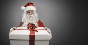 Santa Claus, die ein Geschenk mit rotem Band holt lizenzfreies stockbild