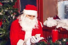 Santa Claus, die ein intelligentes Telefon verwendet Lizenzfreies Stockbild