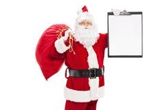 Santa Claus, die ein Klemmbrett hält Lizenzfreie Stockfotos