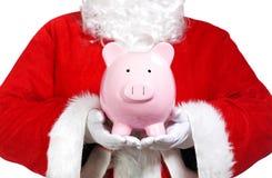 Santa Claus, die ein Sparschwein hält Lizenzfreies Stockbild