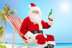 Santa Claus, die eine Flasche Bier auf einem Strand hält Stockfotografie