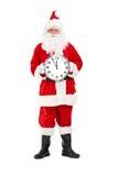 Santa Claus, die eine große Wanduhr hält Lizenzfreie Stockfotografie