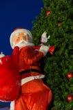 Santa Claus, die eine Tasche auf dem Weihnachtsbaum trägt Lizenzfreies Stockbild
