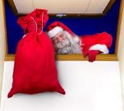 Santa Claus, die eine Tasche im Fenster trägt Lizenzfreie Stockbilder