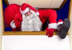 Santa Claus, die eine Tasche zum Fenster trägt Stockbild