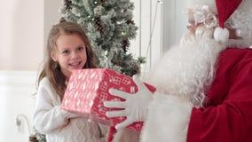 Santa Claus, die einem netten kleinen Mädchen ein freundlich eingewickeltes Geschenk gibt stock video footage