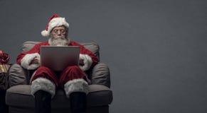 Santa Claus, die an einen Laptop anschließt stockbilder