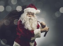 Santa Claus, die einen Sack mit Weihnachtsgeschenken trägt lizenzfreies stockbild