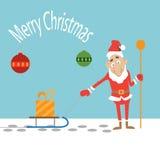 Santa Claus, die einen Schlitten mit einem Geschenk zieht Stockfotografie