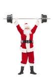 Santa Claus, die einen schweren Barbell anhebt Stockfoto