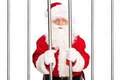 Santa Claus, die in einer Gefängniszelle steht Stockbilder