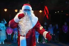 Santa Claus, die einer Gruppe Kindern Geschichten erzählt Weihnachtsmann trägt Geschenke Santa Claus auf Stadium Lizenzfreies Stockbild