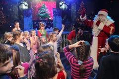 Santa Claus, die einer Gruppe Kindern Geschichten erzählt Weihnachtsmann trägt Geschenke Santa Claus auf Stadium Stockbilder