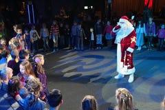 Santa Claus, die einer Gruppe Kindern Geschichten erzählt Weihnachtsmann trägt Geschenke Santa Claus auf Stadium Stockbild