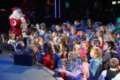 Santa Claus, die einer Gruppe Kindern Geschichten erzählt Weihnachtsmann trägt Geschenke Santa Claus auf Stadium Stockfotos