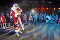 Santa Claus, die einer Gruppe Kindern Geschichten erzählt Weihnachtsmann trägt Geschenke Santa Claus auf Stadium Lizenzfreies Stockfoto