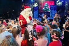 Santa Claus, die einer Gruppe Kindern Geschichten erzählt Weihnachtsmann trägt Geschenke Santa Claus auf Stadium Lizenzfreie Stockfotos