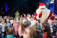 Santa Claus, die einer Gruppe Kindern Geschichten erzählt Weihnachtsmann trägt Geschenke Santa Claus auf Stadium Lizenzfreie Stockfotografie