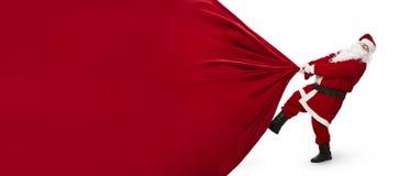 Santa Claus, die enorme Tasche von Geschenken zieht Stockfotografie
