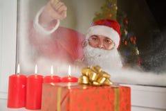 Santa Claus, die am Fenster auf Weihnachten klopft Lizenzfreies Stockfoto