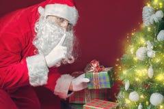Santa Claus, die Geschenkbox oder Geschenk unter Weihnachtsbaum setzt Stockbild