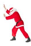 Santa Claus die iets duwen Stock Afbeeldingen