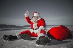 Santa Claus, die im Schnee mit einem Laptop sitzt und wegf schaut Lizenzfreie Stockfotos