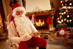 Santa Claus, die im warmen Raum stillsteht und traditionelles Christma isst lizenzfreie stockfotografie