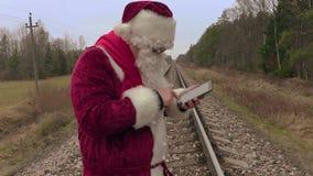 Santa Claus die lijstpc op spoorweg met behulp van stock video