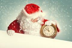 Santa Claus die met witte lege banner een klok houden royalty-vrije stock afbeeldingen