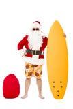 Santa Claus, die mit Brandungsbrett steht Lizenzfreie Stockfotos