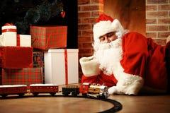 Santa Claus, die mit Spielwaren unter dem Weihnachtsbaum spielt Lizenzfreie Stockfotografie