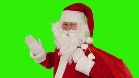 Santa Claus, die seine Tasche, Blicke auf die Kamera trägt, sendet einen Kuss und eine Welle, grünen Schirm, Gesamtlänge auf Lager stock video