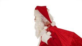 Santa Claus, die seine Tasche, Blicke an der Kamera und Winks, Weiß, Gesamtlänge auf Lager trägt stock footage