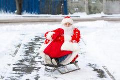 Santa Claus, die in seinem Pferdeschlitten auf einer Stadtstraße während des Weihnachtsfeiertags sitzt lizenzfreies stockfoto