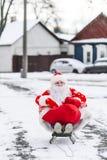 Santa Claus, die in seinem Pferdeschlitten auf einer Stadtstraße während des Weihnachtsfeiertags sitzt stockbilder