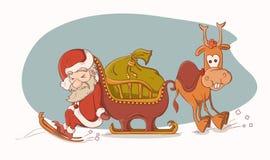 Santa Claus, die seinen Pferdeschlitten drücken und Rudolph Lizenzfreie Stockfotografie