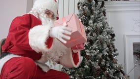 Santa Claus, die seinen Sack öffnet und Geschenke unter den Weihnachtsbaum setzt stockbilder