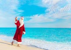 Santa Claus, die am Strand geht, greift herauf das Gestikulieren ab, das conc Weihnachten Lizenzfreies Stockbild