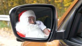 Santa Claus, die am Telefon beim Sitzen in den Auto 50 fps spricht stock video footage