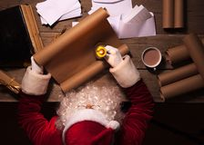 Santa Claus, die am Tisch in seinem Raum sitzt und Weihnachtsbrief oder Wunschliste liest Lizenzfreie Stockbilder