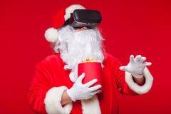 Santa Claus die virtuele werkelijkheidsbeschermende brillen en een rode emmer met popcorn, op een rode achtergrond dragen Kerstmi Stock Afbeelding