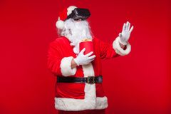 Santa Claus die virtuele werkelijkheidsbeschermende brillen en een rode emmer met popcorn, op een rode achtergrond dragen Kerstmi Stock Foto's
