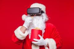 Santa Claus die virtuele werkelijkheidsbeschermende brillen en een rode emmer met popcorn, op een rode achtergrond dragen Kerstmi Stock Fotografie