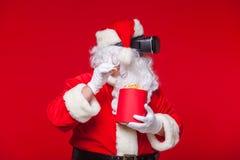 Santa Claus die virtuele werkelijkheidsbeschermende brillen en een rode emmer met popcorn, op een rode achtergrond dragen Kerstmi Royalty-vrije Stock Foto's